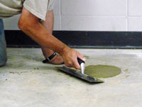 Repairing the cored holes in the concrete slab floor with fresh concrete and cleaning up the Lewiston home.