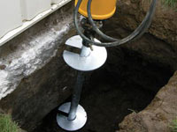 Installing a helical pier system in the earth around a foundation in Nampa