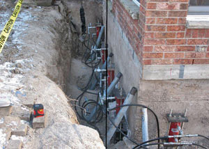 Foundation push piers installed around a house with a foundation settlement issues in Buhl