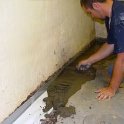 A basement waterproofer installing a perimeter drain system in Eagle