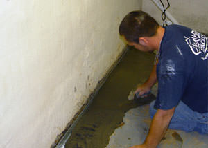 Restoring a concrete slab floor with fresh concrete after jackhammering it and installing a drain system in Rigby.